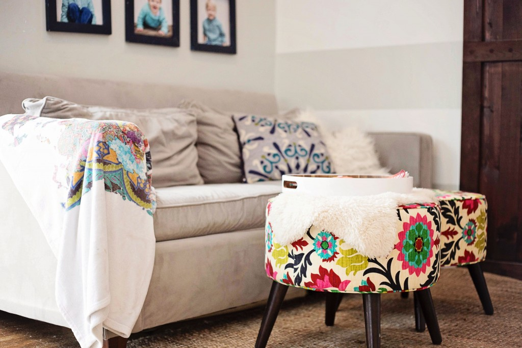 Living room featuring neutral tones with brightly colored ottomans