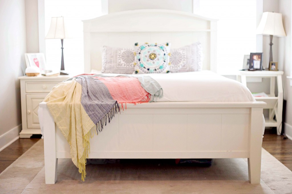 white bed spread with bright pillows
