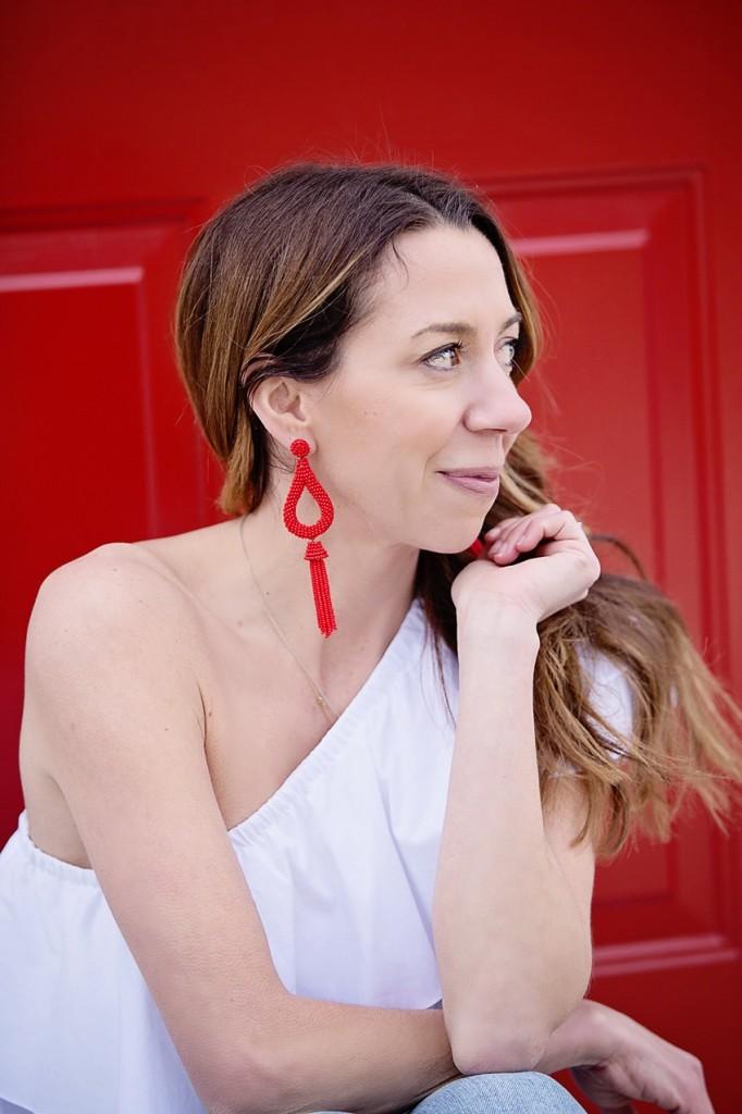 The Motherchic wearing tassel statement earrings from anthropologie