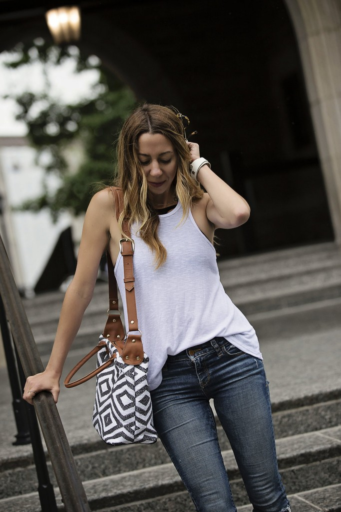 The motherchic wearing white tank and jeans