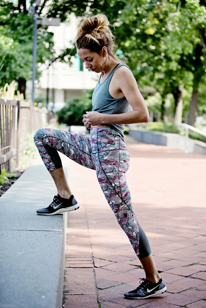 The Motherchic wearing high waist zella leggings and tank top with nike sneakers