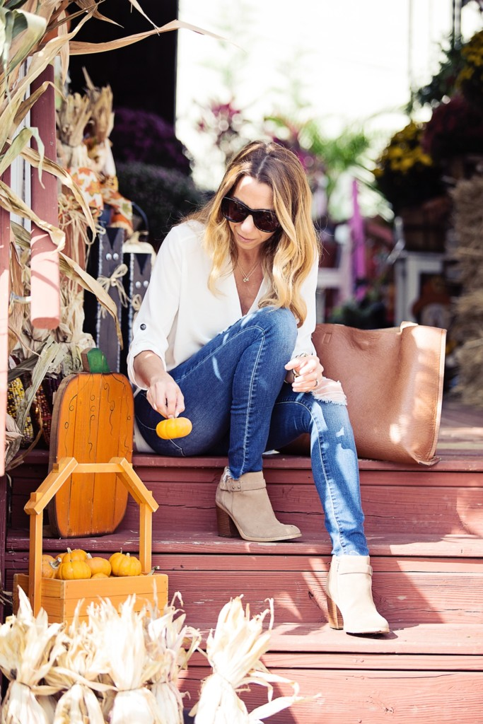 The Motherchic wearing classic fall outfit - white blouse, jeans, and booties