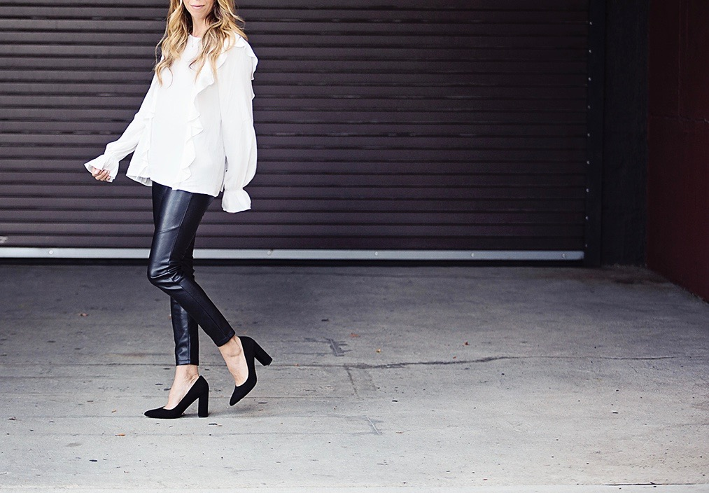 The Motherchic wearing ruffle blouse and free people faux leather pants