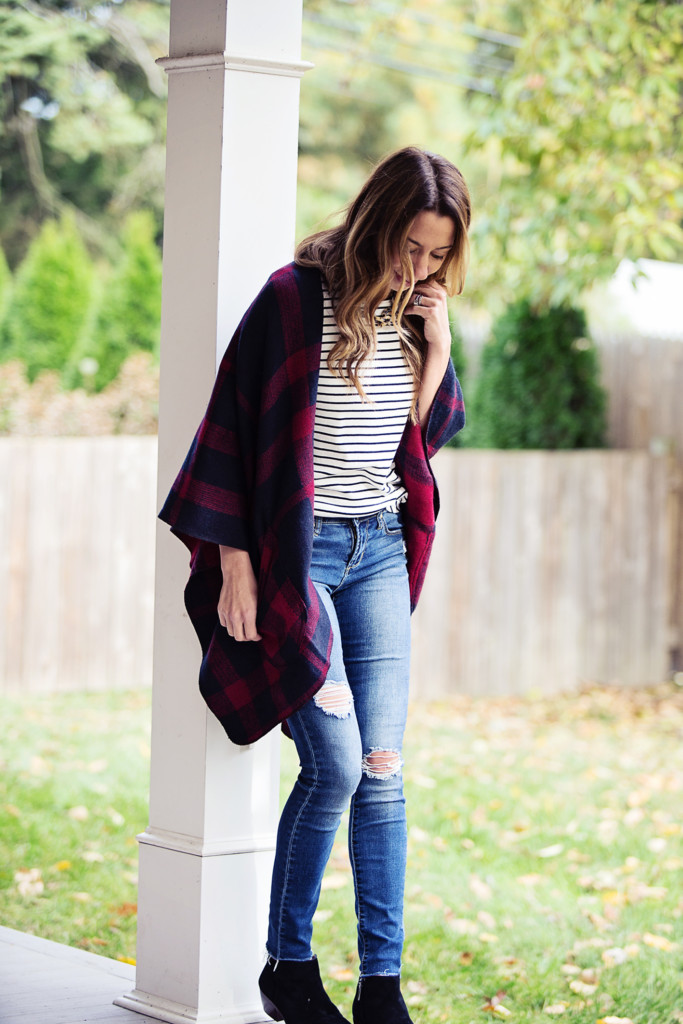 The Motherchic wearing plaid cape and distressed jeans