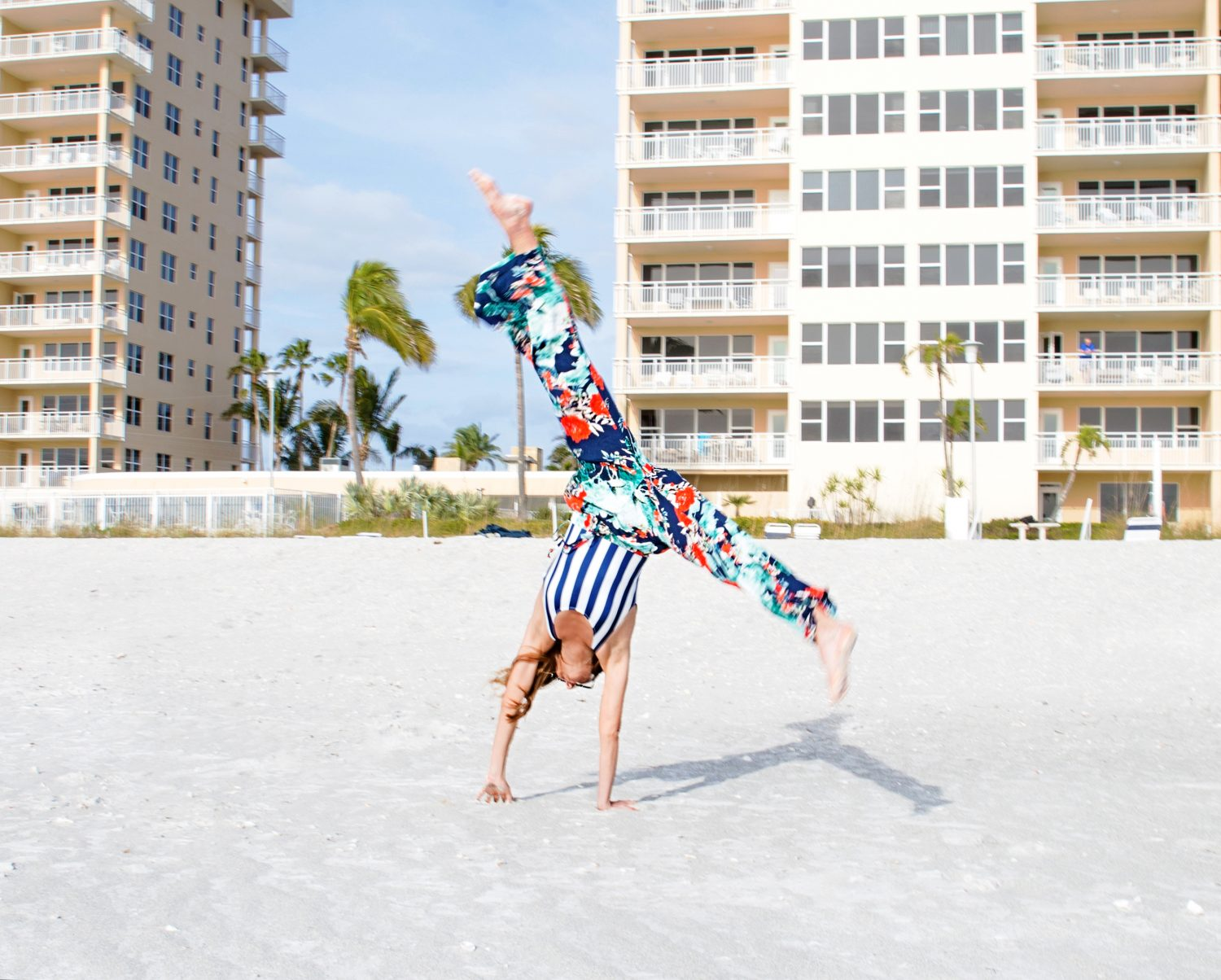 The Motherchic wearing solid and striped one piece bathing suit