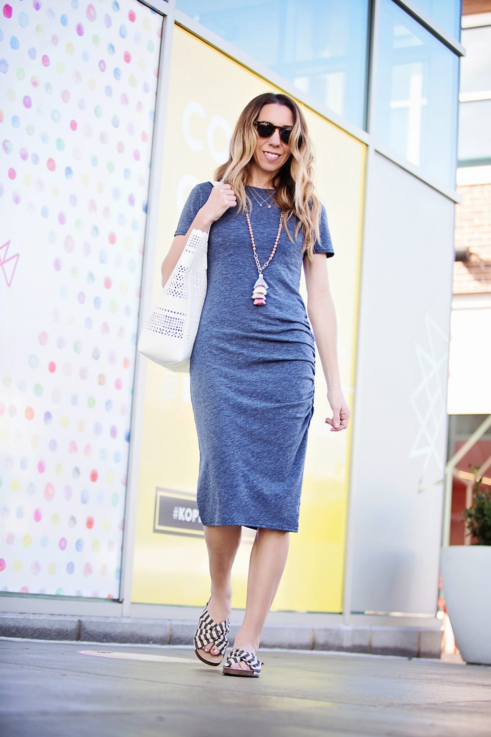 The Motherchic wearing side ruched body con dress