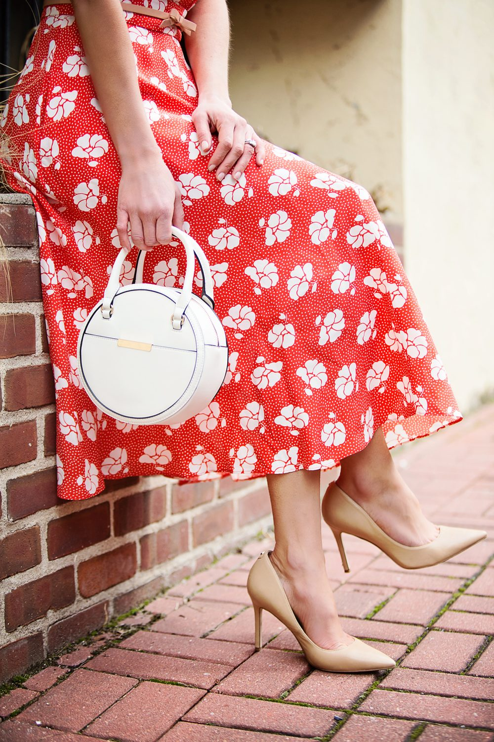 The Motherchic wearing floral dress with nude pumps and circle bag