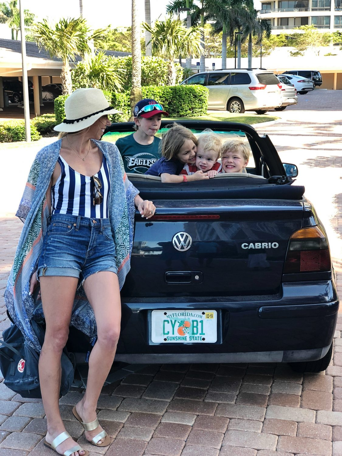 The motherchic wearing solid & striped bathing suit