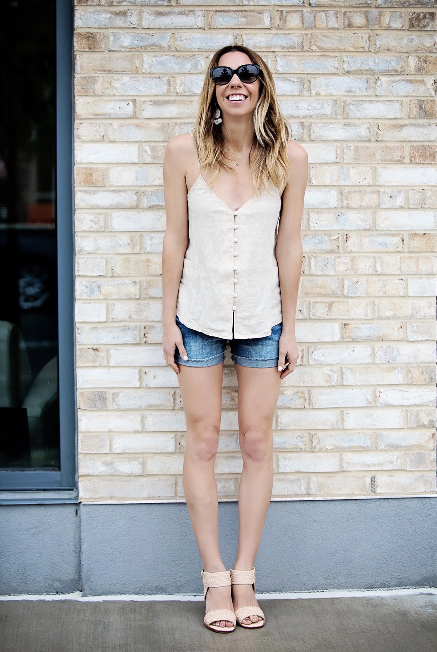 The Motherchic wearing buttoned cami and denim shorts