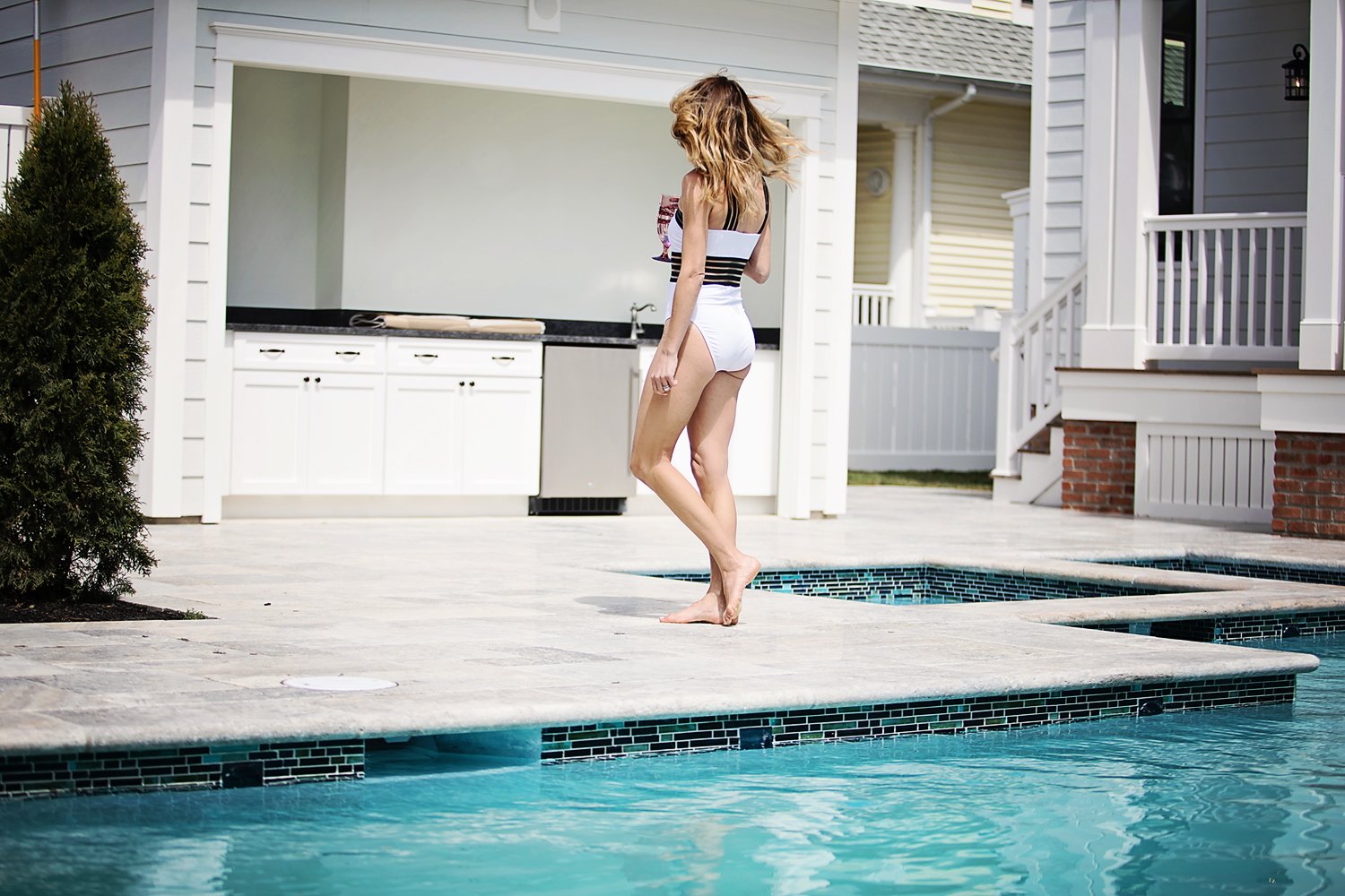 The Motherchic wearing Kenneth Cole Reaction swimsuit from Macy's