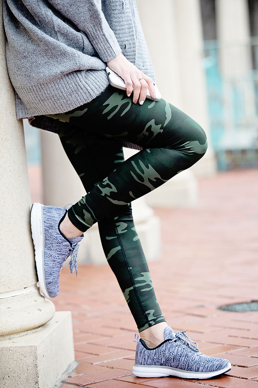 The Motherchic wearing easy travel outfit of camo leggings and APL sneakers from Nordstrom