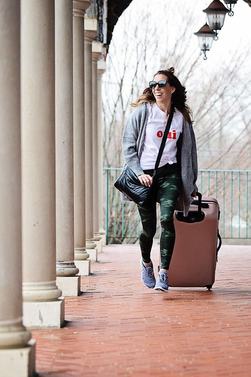 The Motherchic wearing easy travel outfit of camo leggings and open cardigan from Nordstrom