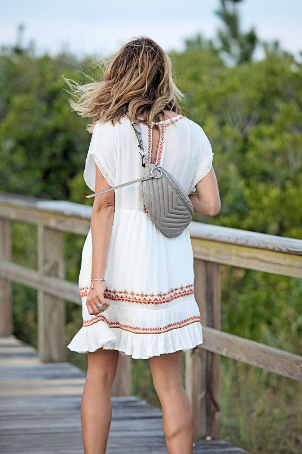 The Motherchic wearing free people dress and Rebecca Minkoff belt bag