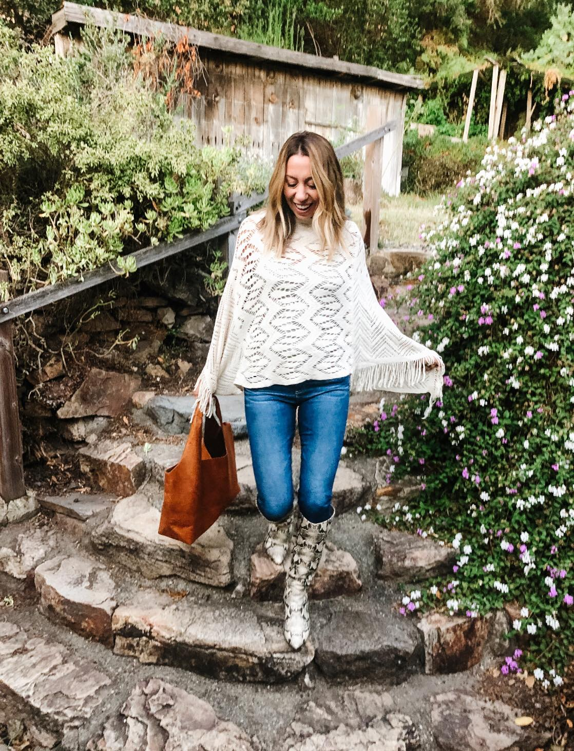 The motherchic wearing anthropologie poncho and snakeskin booties