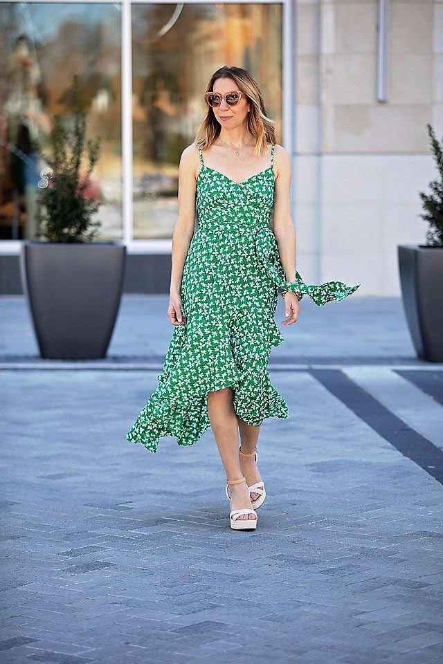 the motherchic wearing green wrap dress wedding guest